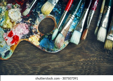 Artist paint brushes and palette on wooden background