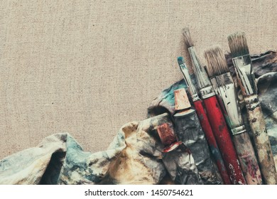Artist paint brushes, paint tubes closeup on brown linen canvas.