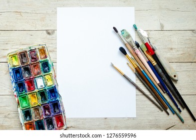 Artist paint brushes and watercolor paintbox on wooden background with empty sheet of paper. Instruments and tools for creative leisure. Paintings art concept mockup. Top view. Copy space. Flat lay.