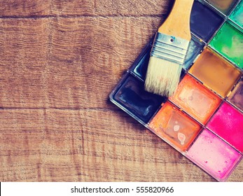 Artist paintbrushes on water colors palette .Studio shot on wooden background and vintage styled. Photo of Art or abstract concept.