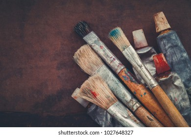 Artist paintbrushes, paint tubes closeup on brown canvas background. Copy space for text.