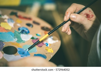 artist painting with acrylic colors and mixing tones on the pallet. blur background abstract photo - vintage effect