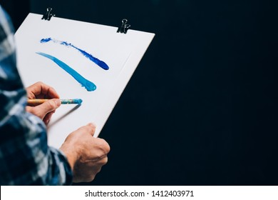 Artist painting. Board panel in man hands. Sudden inspiration creativity artistry. Guy making paint brush strokes on paper.