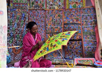 An artist is painting a colorful umbrella sitting in front of a bright colorful background made of hand painted wall art on street. Indian rural lifestyle, art and handicrafts