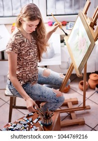 Artist painting on easel in studio. Happy authentic girl paints with brush in morning sunlight dawn light toning. Competition on drawing. Selection of brushes for watercolor painting. Teenager