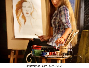 Artist painting on easel in studio. Girl paints portrait of woman with brush. Female painter seen from behind. Indoor home interior for handmade crafts.