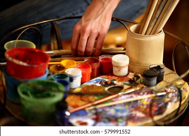Artist painting on easel in studio. Cropped shot of hands paints of woman with brush. Indoor home interior for handmade crafts.