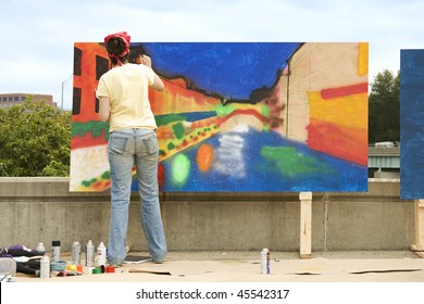 Artist painting on a wooden plywood canvas at an outdoor festival