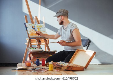 artist painting a picture in a studio.