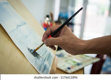 Artist painting watercolor with a round brush in the studio