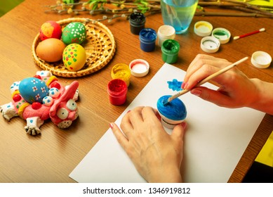 The artist paints Easter religious items. Chicken egg, prepared for coloring, is in the basket. Branches of willow and lilac with blooming green leaves. Paint in a jar with brushes and a glass of wate