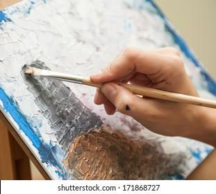 artist paints oil painting on canvas