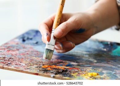 Artist paints a picture of oil paint brush in hand with palette close up.