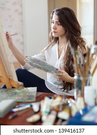 artist paints picture on canvas with oil paints in her workshop