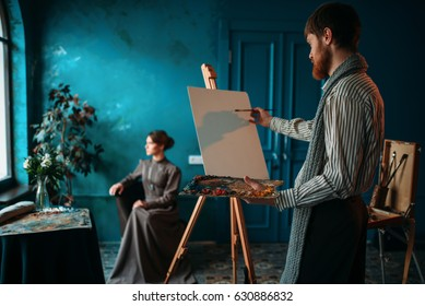 Artist with palette and brush in front of easel