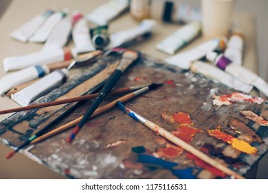 Artist palette, close-up. Brushes with paints, various tools of artist in working disorder. Creative workshop, painting, art