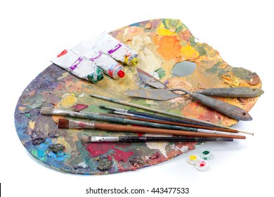 Artist palette with various colors tubes of oil paints and brushes isolated on white background