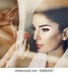 The artist puts makeup for bride