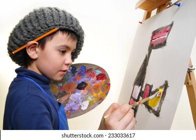 artist school boy painting brush watercolors portrait on a easel