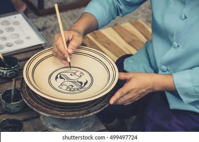 Artist sketch drawing paint pattern in earthenware, making of handcraft pottery in Sukhothai, Thailand.