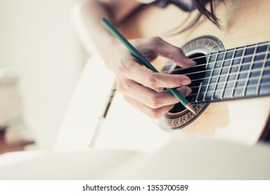 artist songwriter thinking and writing notes,lyrics in book at studio.man playing live acoustic guitar.concept for musician creative.artist composer work process.people relaxing time with instrument