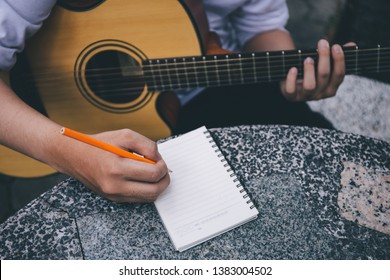 artist songwriter thinking and writing notes,lyrics in book at studio.man playing live acoustic guitar.concept for musician creative.artist composer in work process.people relaxing with instrument