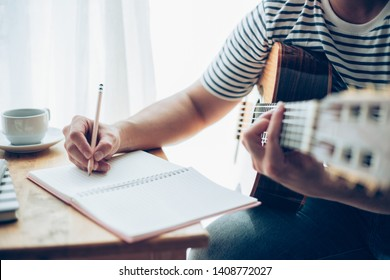 artist songwriter thinking and writing notes,lyrics in book at studio.man playing live acoustic guitar.concept for musician creative.composer in work process.people relaxing time with instrument
