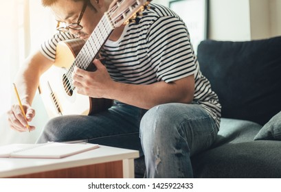 artist songwriter thinking writing notes,lyrics in book at studio.man playing live acoustic guitar.concept for musician creative.composer in work process.people relaxing time with instrument
