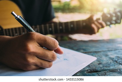 artist songwriter thinking writing notes,lyrics in book at studio.man playing live acoustic guitar relax chill.concept for musician creative.composer work process.people relaxing time with instrument.