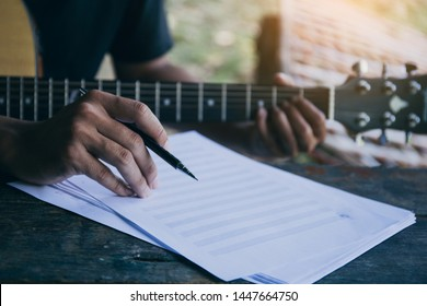 artist songwriter thinking writing notes,lyrics in book at studio.man playing live acoustic guitar relax chill.concept for musician creative.composer in work process.people relaxing time