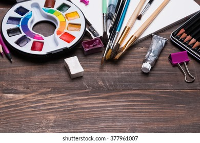 Artist supplies on the wooden background, top view