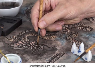 Artist using calligraphy brush and block ink to paint a traditional Chinese dragon