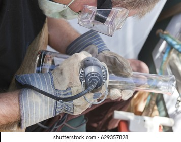 Artist using dremel, etching design on glass.