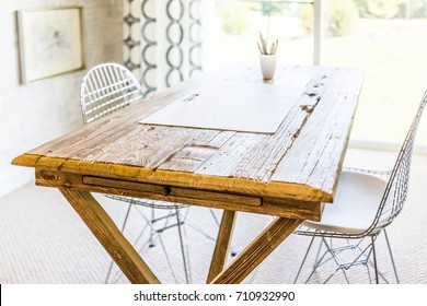 Artist wooden table with drawing boars and chairs by sunny window in house, home or apartment