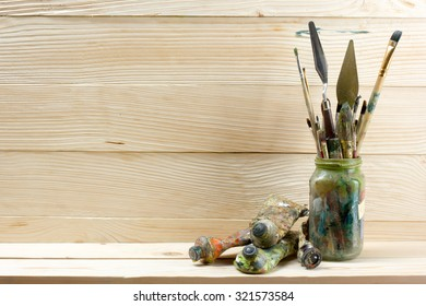 Artistic, artist, art. Used artist paintbrushes mastehin on wood background. Back to school, copy space. Education background.