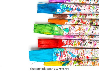 Artistic background. Artist paintbrushes with colorful watercolor paint stains isolated on white background.