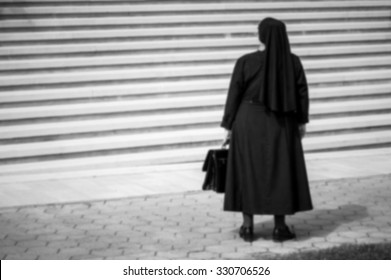 Artistic black and white blur edit catholic nun in front of high white stairs. Concept of decision making, high problems, challenges.