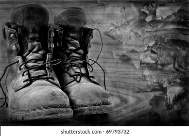 Artistic black and white image of rugged  boots on wood textured background.