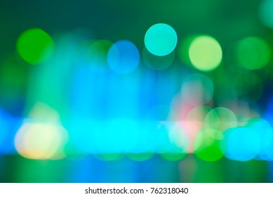 Artistic bokeh background. Defocused circular blue, green and yellow lights. Without black color on background.