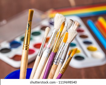 Artistic brushes in a cup close-up against a background of watercolor sets
