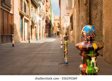 Artistic colorful decorated bollards at an old street in Tarragona, Catalonia, Mediterranean Spain.