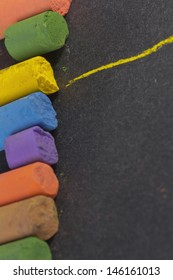 artistic colorful pastels in a row, with a yellow line drawn on