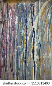 Artistic colourful ink and paint drips on a silver metallic textured background in an industrial artists studio. perfect for artistic backgrounds.