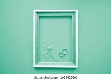 Artistic composition. Wedding rings and a flower in a wooden frame of soft turquoise color (Tiffany). The view from the top. Mortgage the apartment.