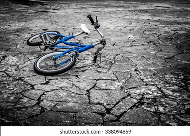 Artistic dark vintage edit of a left children's bicycle on a cracked concrete floor, concept of interrupted childhood, abduction etc. Artistic selective color, blue on black and white background.