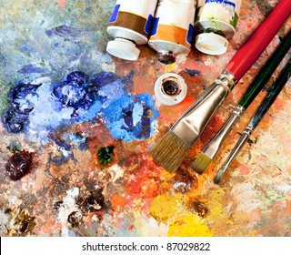 Artistic equipment: paint, brushes, spatula and art palette