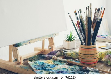 Artistic equipment in studio: canvas on wooden easel, paint brushes, paints and used palette.  Copy space for text.