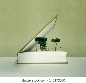 Artistic fantasy open book with the pop up effect with trees, field and traffic light