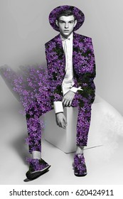 artistic fashion vogue image of a man in a hat and black suit. collage with a flying flowers on his clothes