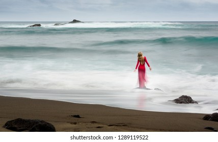Artistic fine art picture about a red, long dressed beautiful blonde woman, who stands on a beach rock in the water.